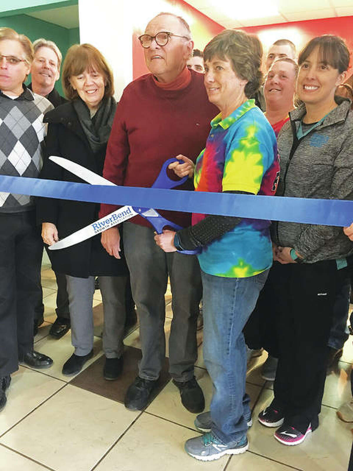 Alton Mayor Brant Walker, far left, and Godfrey Mayor Mike McCormick standing next to his wife, Linda McCormick, holding giant scissors, who is the owner of the new Cookie Express store at Alton Square Mall, located in the lower level.