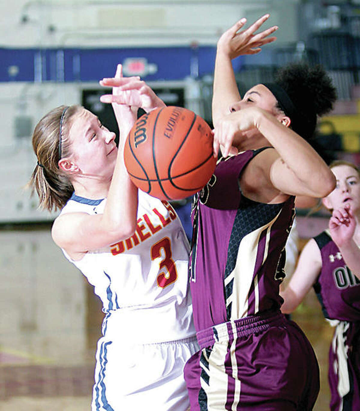 Roxana's Emma Lucas, left, gets tangled up with EA-WR's Kate Baskin while going up for a shot Wednesday night in Roxana.