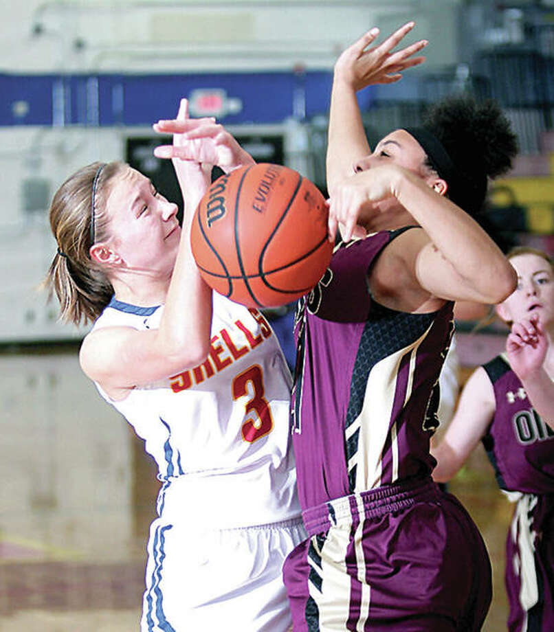 Roxana's Emma Lucas, left, gets tangled up with EA-WR's Kate Baskin while going up for a shot Wednesday night in Roxana. Photo: James B. Ritter | For The Telegraph