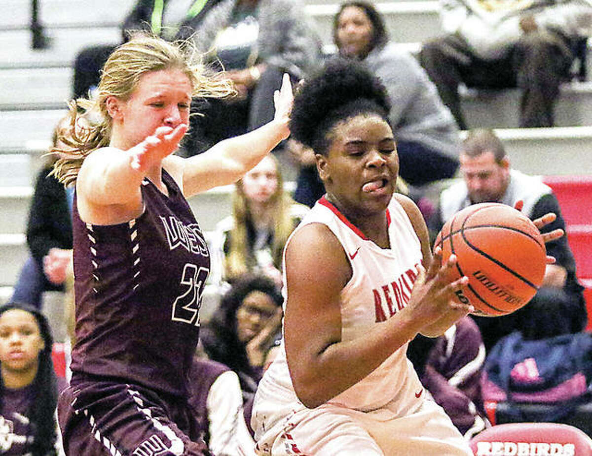 Chr'shonna Hickman of Alton, right, drives against Belleville West's Jessica Coughlin in SWC action Thursday night at Alton High. West won 37-36.