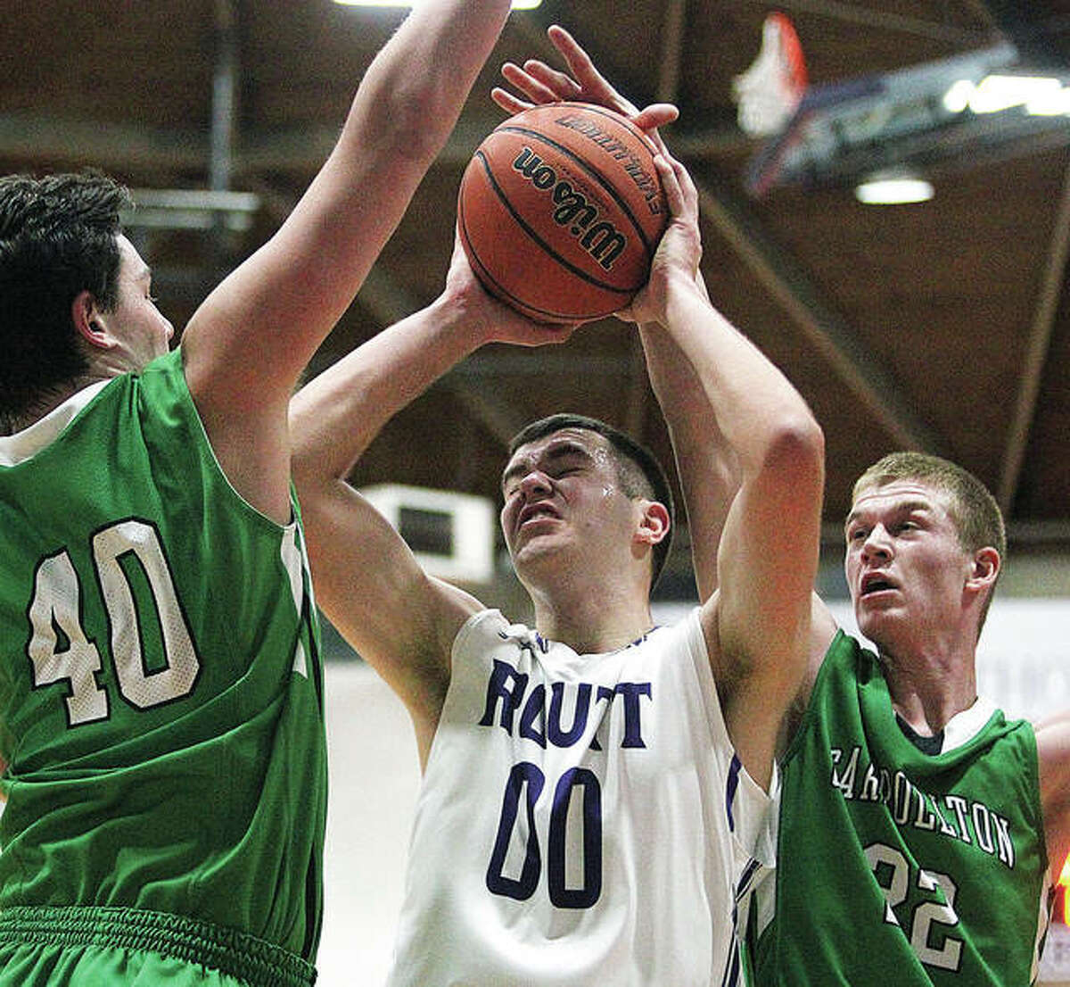 Carrollton's Gabe Jones (22) reaches up to block a shot by Routt's Brooks Moore during a game Thursday night in Jacksonville.