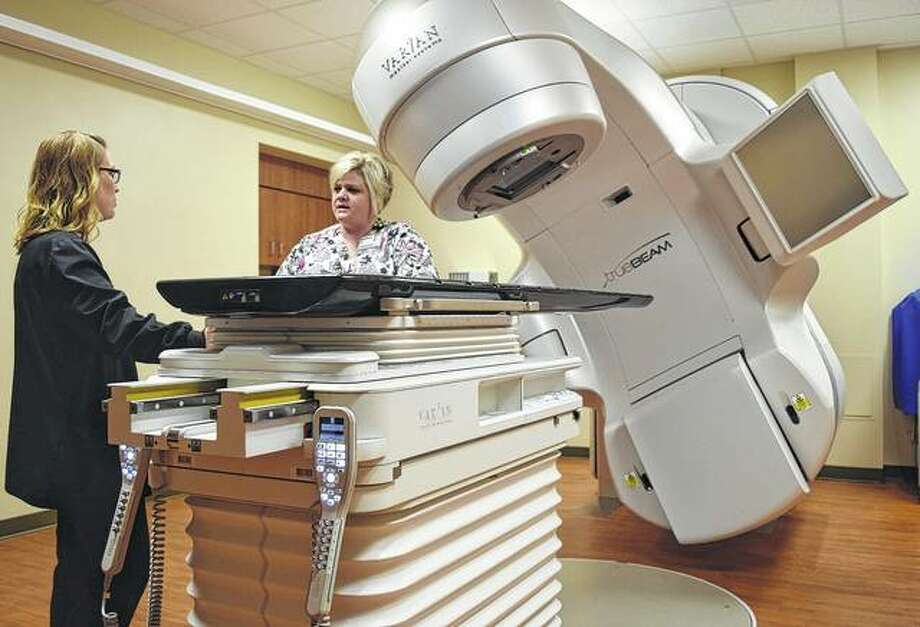 Radiation therapists Laura Bushnell (left) and Ashli Malin stand near a linear accelerator — which supplies an X-ray beam used in treating cancer — at the Passavant Radiation Oncology Center, which opens Monday. Photo: Greg Olson | Journal-Courier