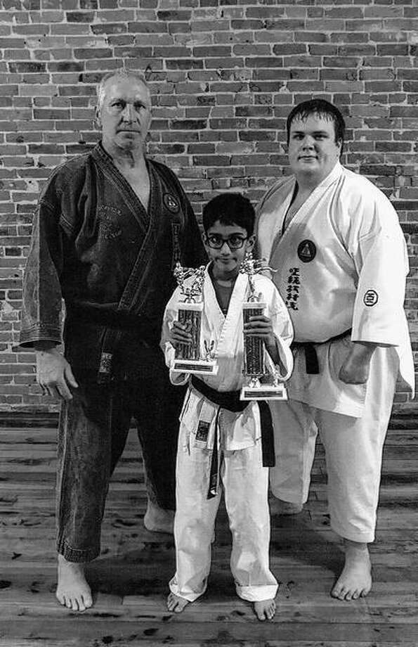 Akash Sudhir (center) participated in the USKK karate tournament on March 25 in Pekin. He placed second in kata and third in kumite in the boys 9-10 blue belt division. Standing behind Akash are Sensei Mike Nicholson (left) and Sensei Matt Gust.
