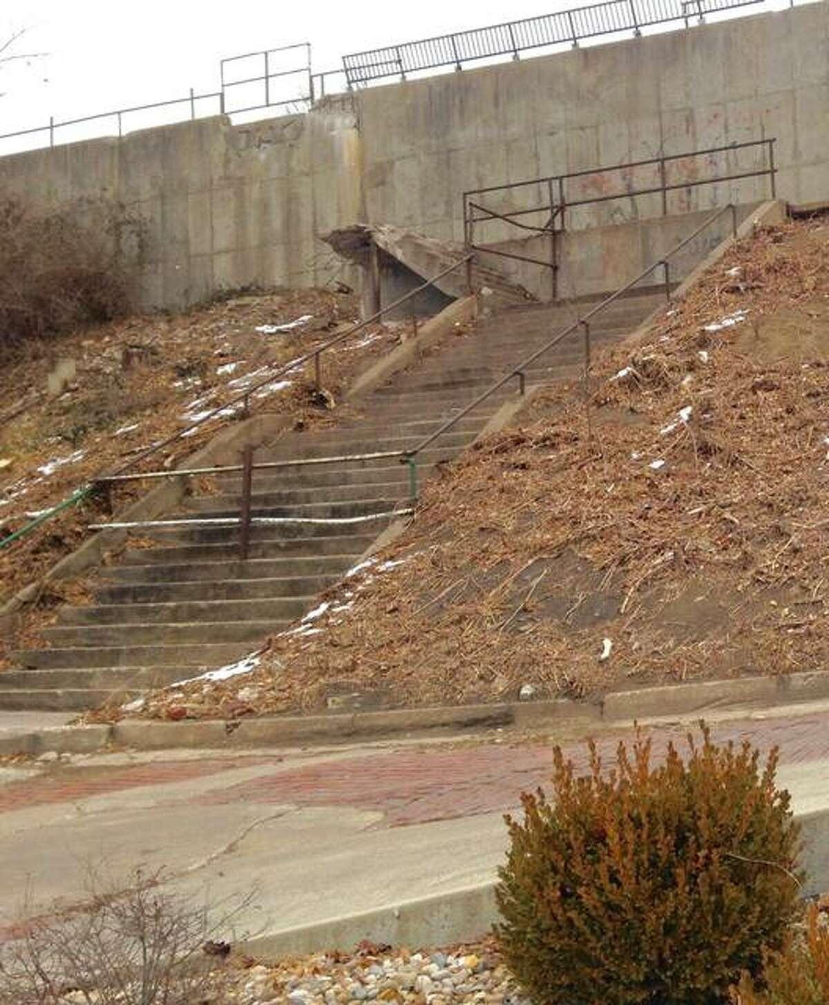 Alton Public Works and Park departments' workers recently cleared a hill of some plant growth Downtown by Fourth Street, below Market Street, to determine what repairs are needed to a graffiti-defaced wall, staircase that ends mid-air and a sidewalk that runs from the steps to the south.