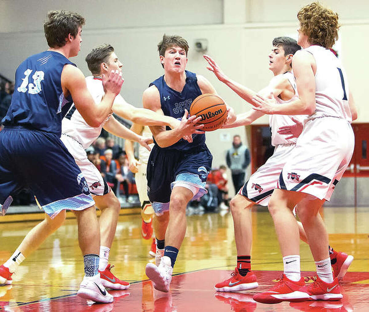 Jersey's Blake Wittman (middle) splits Triad's defense to drive the lane while teammate Lucas Ross (13) looks on during Friday night's Mississippi Valley Conference boys basketball game at Triad.