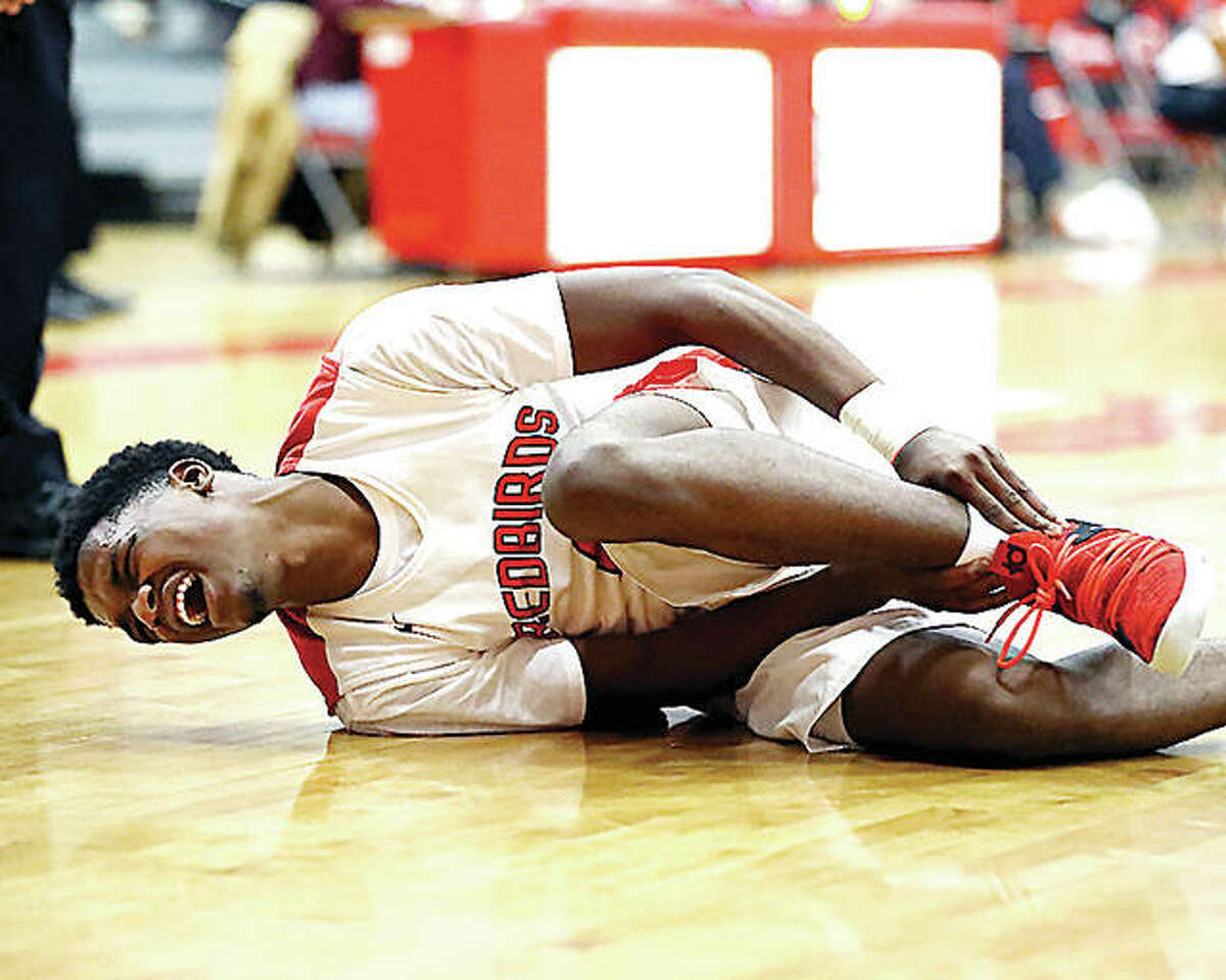 Alton's Kevin Caldwell falls to the court holding his ankle during Friday night's game against Belleville West at Alton High School. He did not return to the game. West won, 65-40.