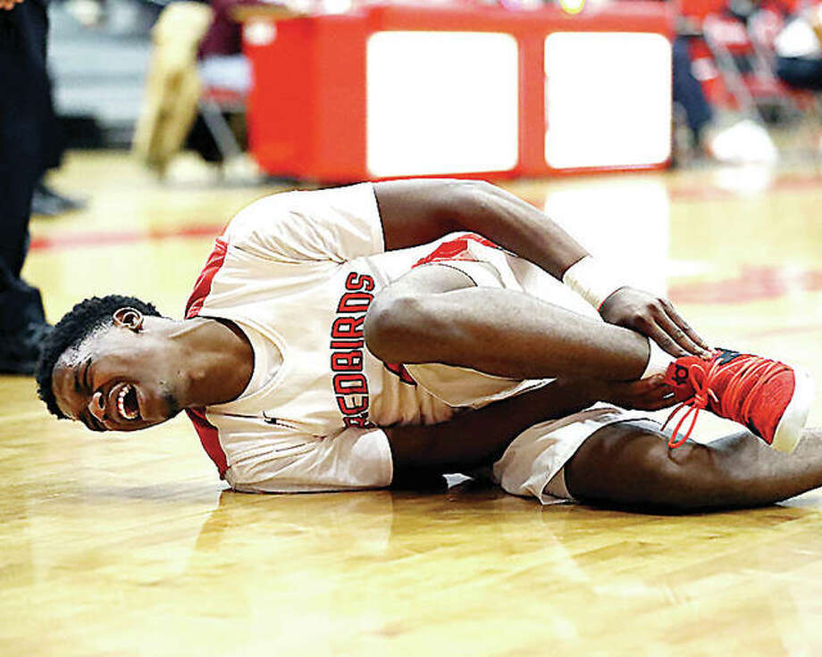 Alton's Kevin Caldwell falls to the court holding his ankle during Friday night's game against Belleville West at Alton High School. He did not return to the game. West won, 65-40. Photo: Billy Hurst | For The Telegraph