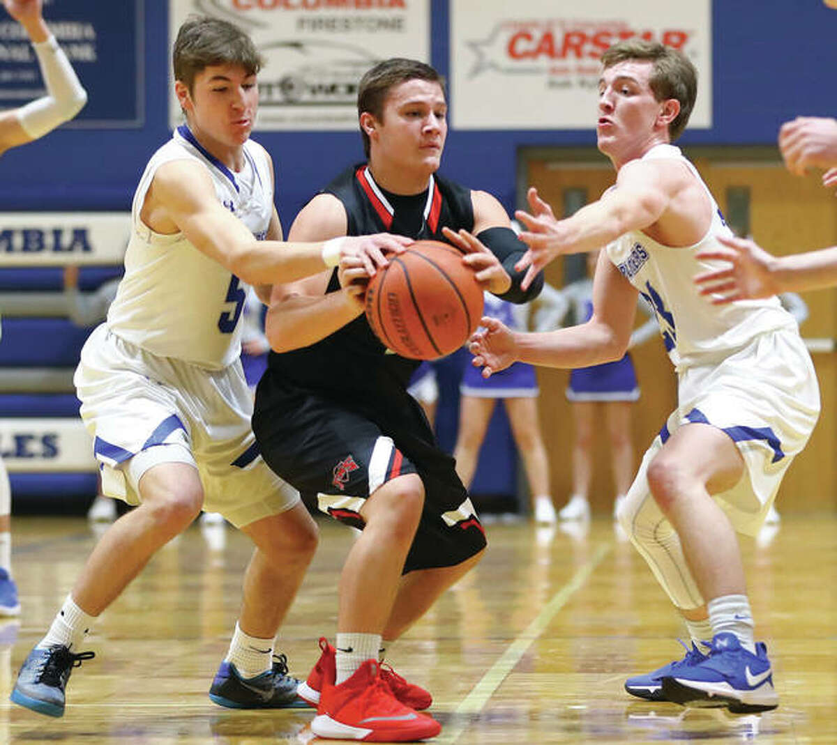 Marquette Catholic's Chris Hartrich (left) and Reagan Snider (right) take the ball away from Triad's Trevor Nott during a game in the Columbia Holiday Tournament on Dec. 28 in Columbia. The Explorers opened the new year Saturday night in Breese and defeated Mater Dei to improve to 15-0.