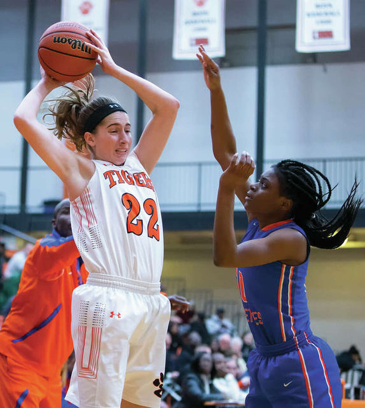 Edwardsville's Kate Martin (left) looks inside for a teammate over East St. Louis' Rokelle Stanley during a Tigers' victory Dec. 20 in Edwardsville. The 16-0 Tigers got by a challenging stretch of their schedule unscathed and are ranked No. 1 in the Class 4A state poll.