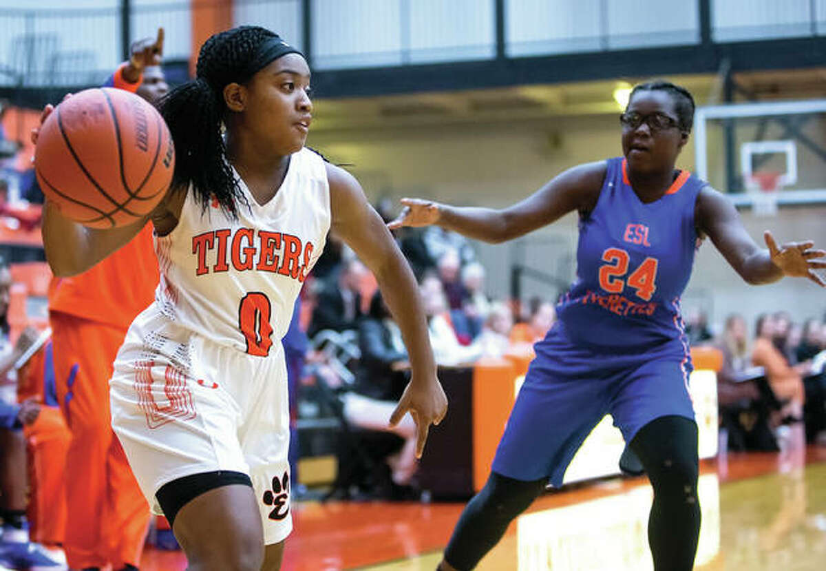Edwardsville' point guard Quiera Love (left) makes a pass during SWC play against East St. Louis earlier this season in Edwardsville. Coming off a championship in their first visit to the prestigious Visitation Christmas Tournament, Edwardsville is 16-0 and ranked No. 1 in the state.