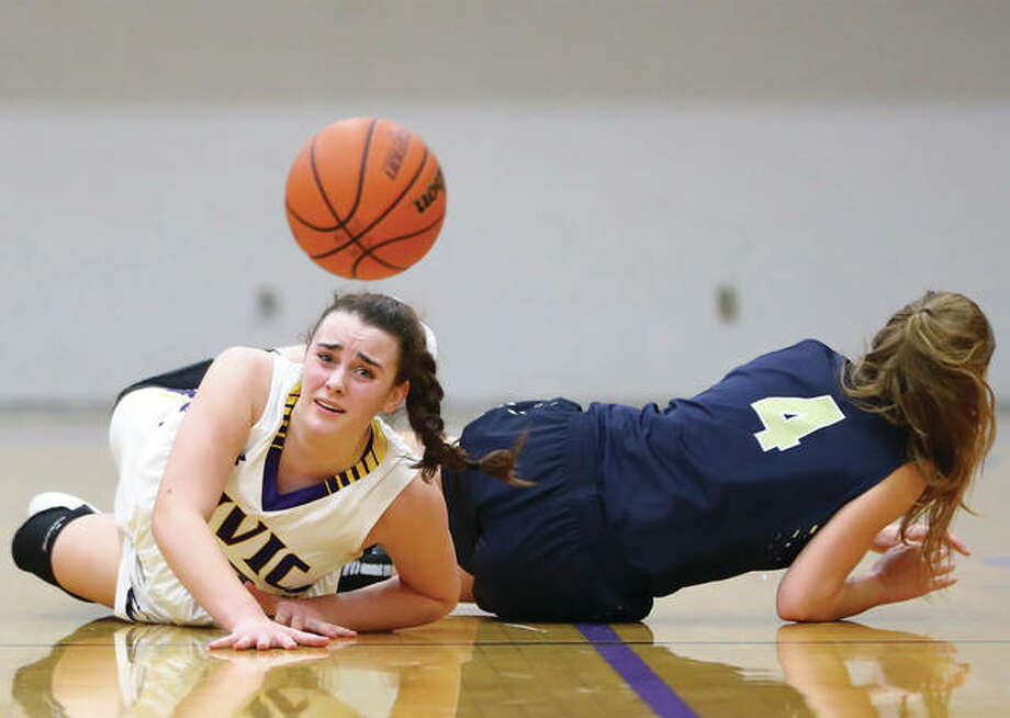 CM's Anna Hall (left) falls to the court as she battles for a loose ball with Teutopolis' Jolene Bueker during a clash of state-ranked girls basketball teams Monday night in Bethalto. The Eagles won 55-42 pushing their record to 17-1, while dropping the Wooden Shoes to 19-2. Photo: Billy Hurst / For The Telegraph