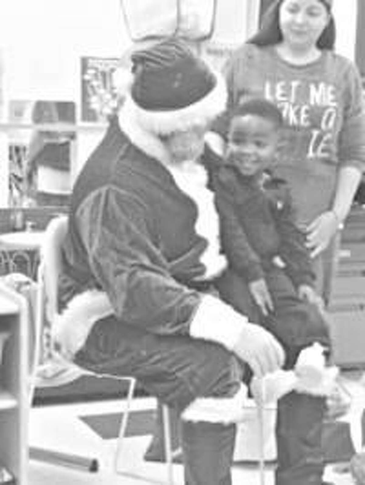 A Head Start participant sits on Santa's lap during the SIUE School of Nursing WE CARE Clinic's Christmas event Dec. 19.
