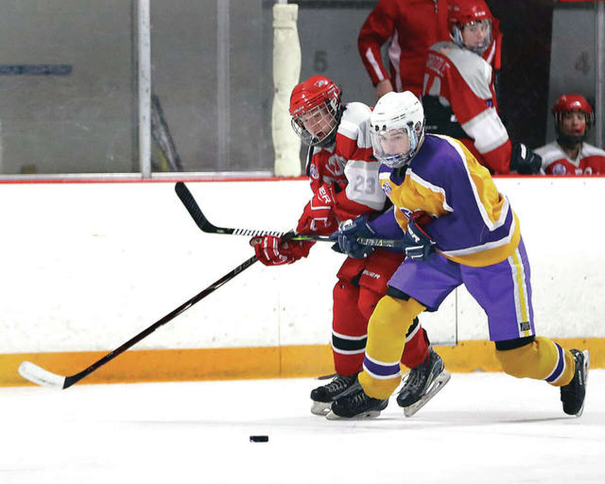 Bethalto's Nolan Kahl, right, and Alton's Zach Carter battle for a loose puck during a game earlier this season at East Alton Ice Arena. Bethalto and Alton will compete in Class 1A the rest of the season after the annual late-season re-seeding of the Mississippi Valley Club Hockey Association.