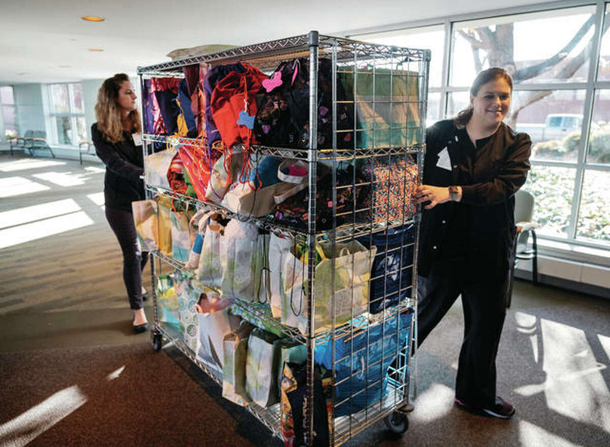 """In this Dec. 21, 2017 photo, Carbondale Memorial Hospital staff members roll a cart full of """"hope bags"""" into the hospital in Carbondale, Ill. Each bag contains a book, stuffed animal and a toy or activity. At 20 weeks pregnant in 2016 Christi Kearns went in for a regular checkup and learned her baby had no heartbeat. doctors at Carbondale Memorial Hospital induced labor. Her daughter, Elle, was born the next day. Through her her family's loss they started the Elle Project that delivers """"hope bags"""" for children admitted to the hospital."""