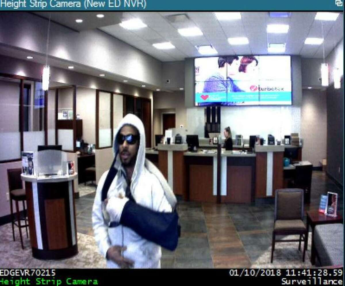 A surveillance image of the suspected bank robber shows his left arm in a sling.