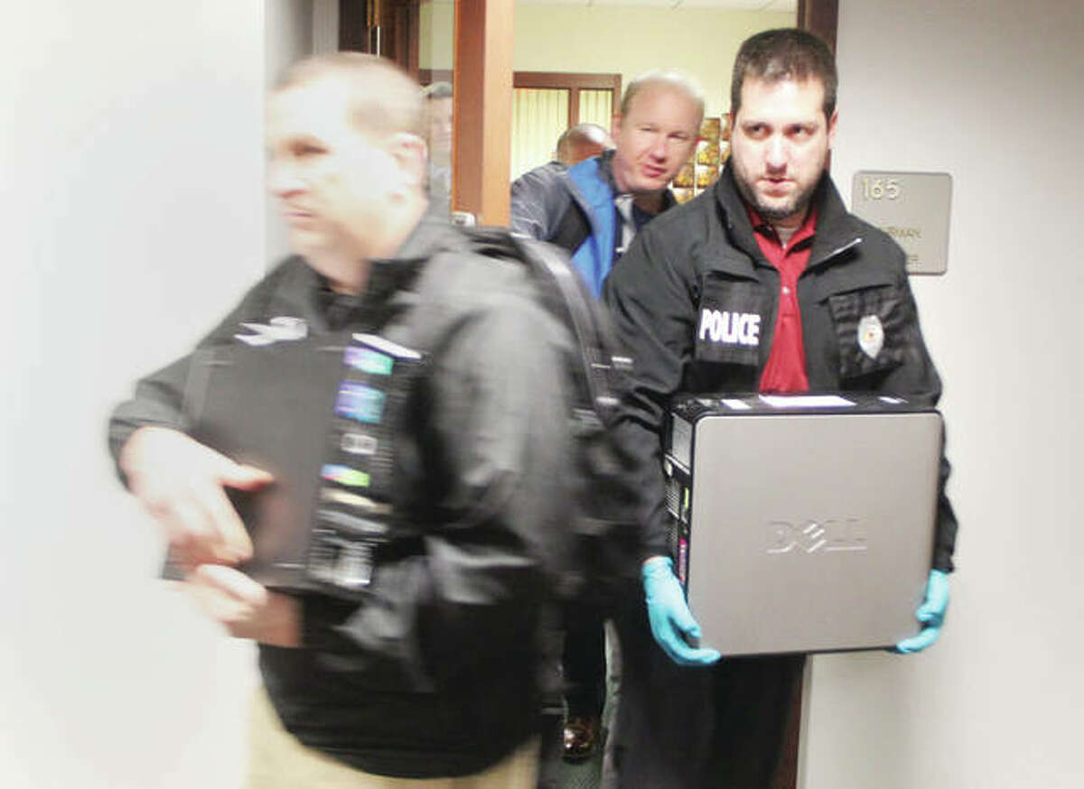 """Police officers remove items from the Madison County Board office after serving search warrants Wednesday afternoon. Warrants were also served on the county's IT office, and the office of Communications Manager Cynthia Ellis. The raid was part of a larger investigation by a newly-formed """"Madison County Public Corruption Task Force."""""""