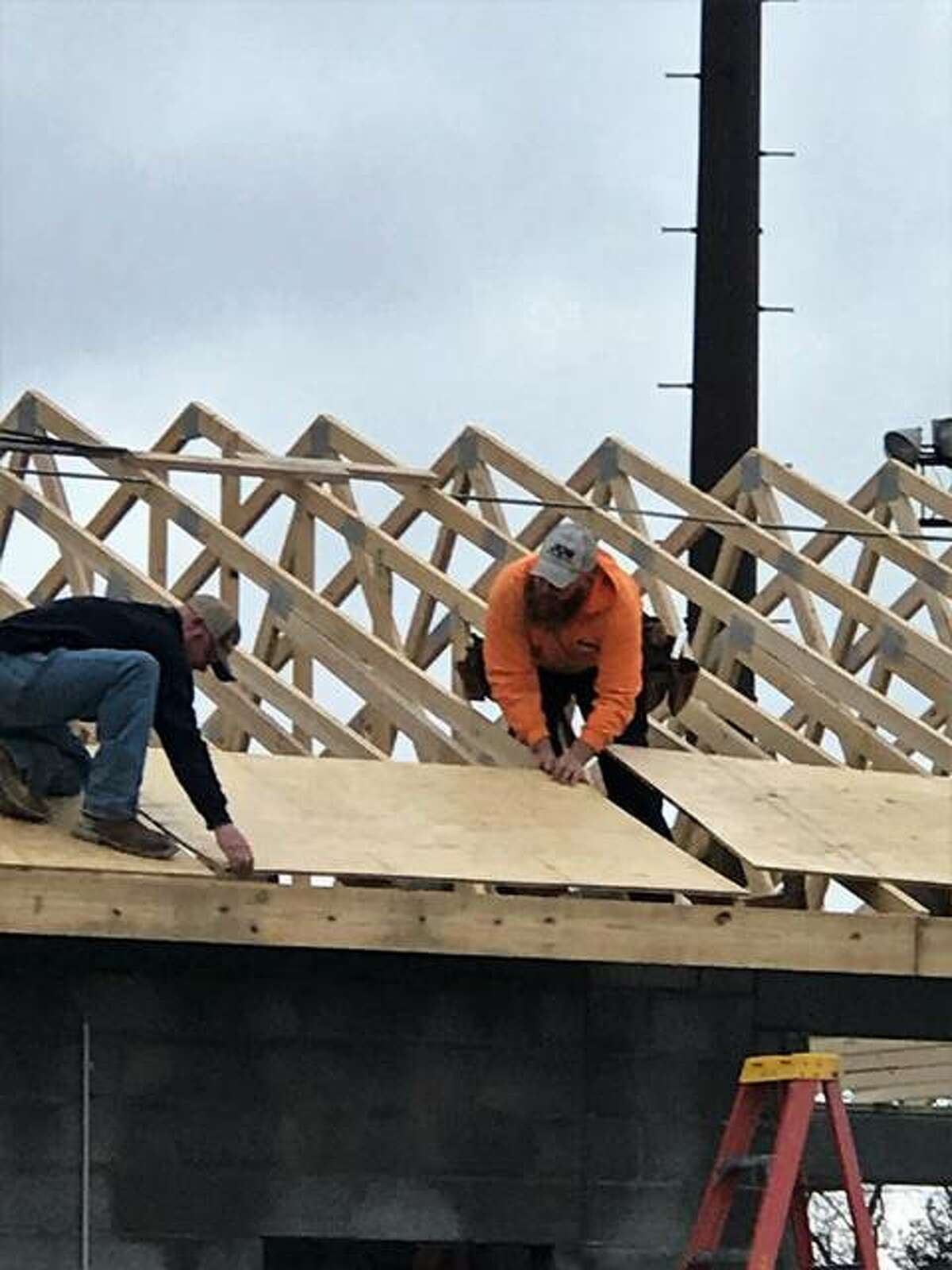 Volunteers from Jun Construction of Godfrey took advantage of Wednesday's warmer temperatures and installed roof trusses and sheeting on the evolving concession stand at Gordon F. Moore Community Park in Alton.