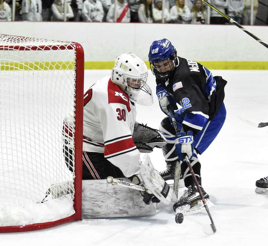 New Canaan goalie Dylan Shane deflects a shot by Darien Bennett McDermott (22) in the first period during an FCIAC Boys Hockey game at the Darien Ice House in Darien, Conn. on Friday, Feb. 9, 2018. Darien defeated New Canaan 3-2 in OT. Photo: Matthew Brown / Hearst Connecticut Media / Stamford Advocate