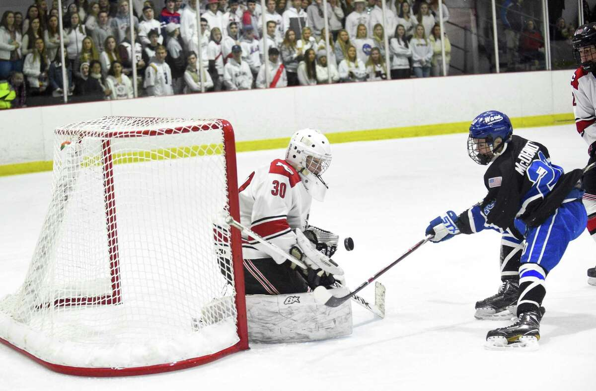 New Canaan goalie Dylan Shane deflects a shot by Darien Bennett McDermott (22) in the first period during an FCIAC Boys Hockey game at the Darien Ice House in Darien, Conn. on Friday, Feb. 9, 2018. Darien defeated New Canaan 3-2 in OT.