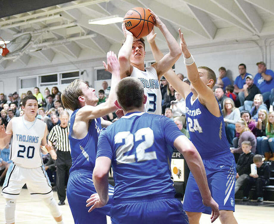 Triopia's Zach Thompson jumps over a crowd of North Greene Spartans for a shot Wednesday night at the Winchester Invitational. Thompson scored five points, but North Greene beat Triopia 55-53. Photo: Audrey Clayton, Journal-Courier | For The Telegraph