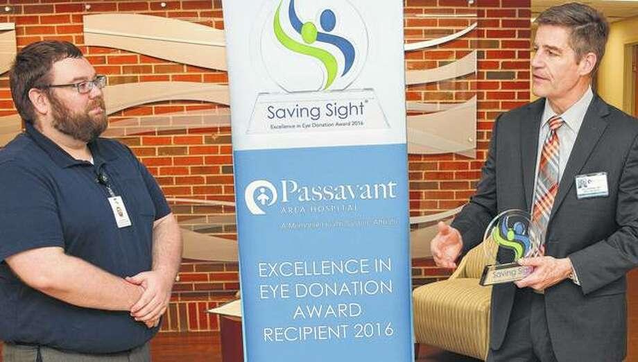 Richard Hamilton (left), parter relations coordinator for Saving Sight, listens Monday to a speech by Passavant Area Hospital CEO Harry Schmidt. Photo: Photo Provided