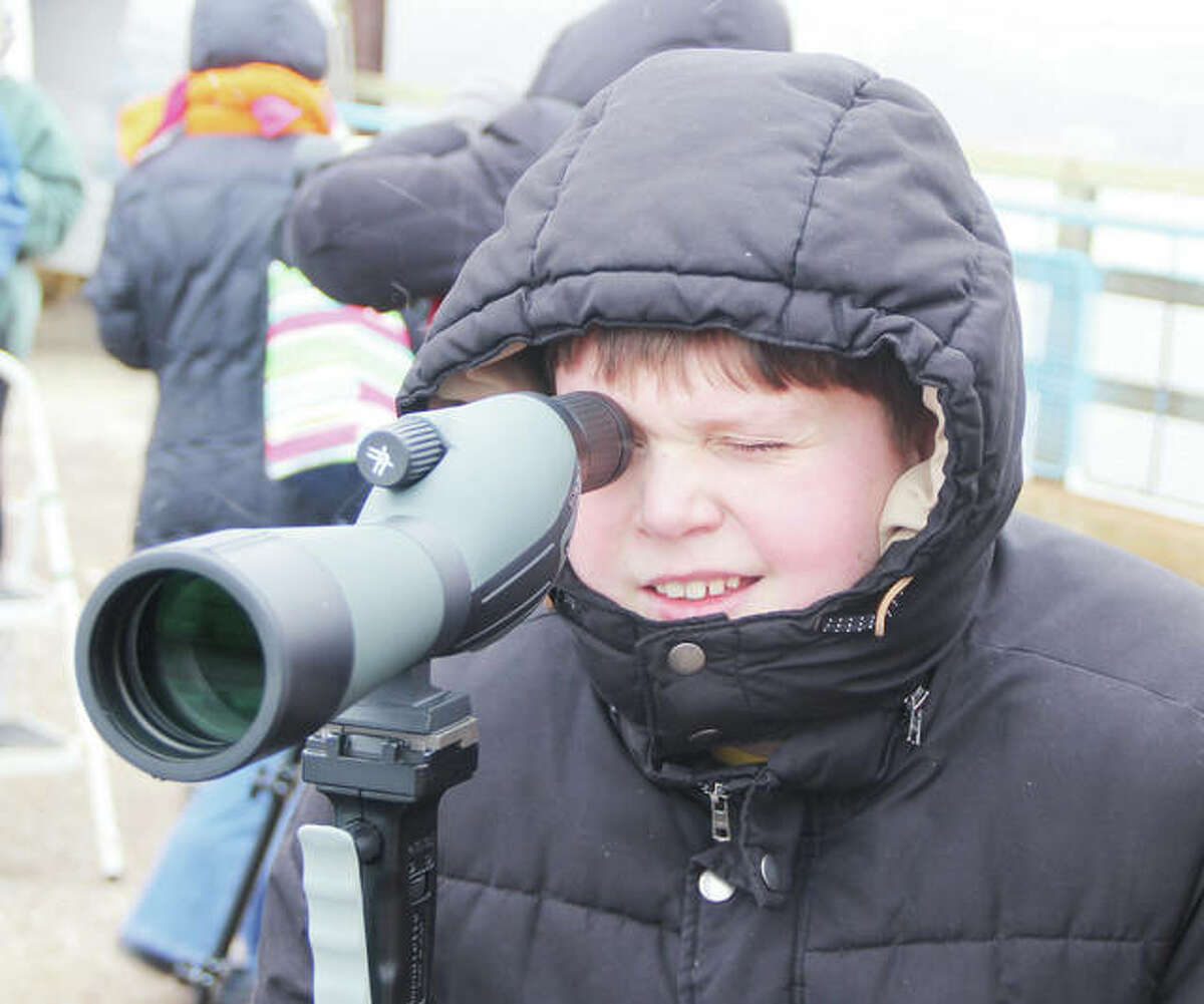 Nathan Klaas, 11, of Edwardsville, a student at Zion Lutheran School in Bethalto, looks at a bald eagle nest while using a spotting scope on the Old Chain of Rocks Bridge Friday morning. About 25 students, teachers and chaperones came out for an educational event on the bridge as part of Eagle Days. The event will be open to the public from 9 a.m. to 3 p.m. Saturday and Sunday, and include live eagle demonstrations by the World Bird Sanctuary, a chance to view bald eagles in the wild, and other activities.