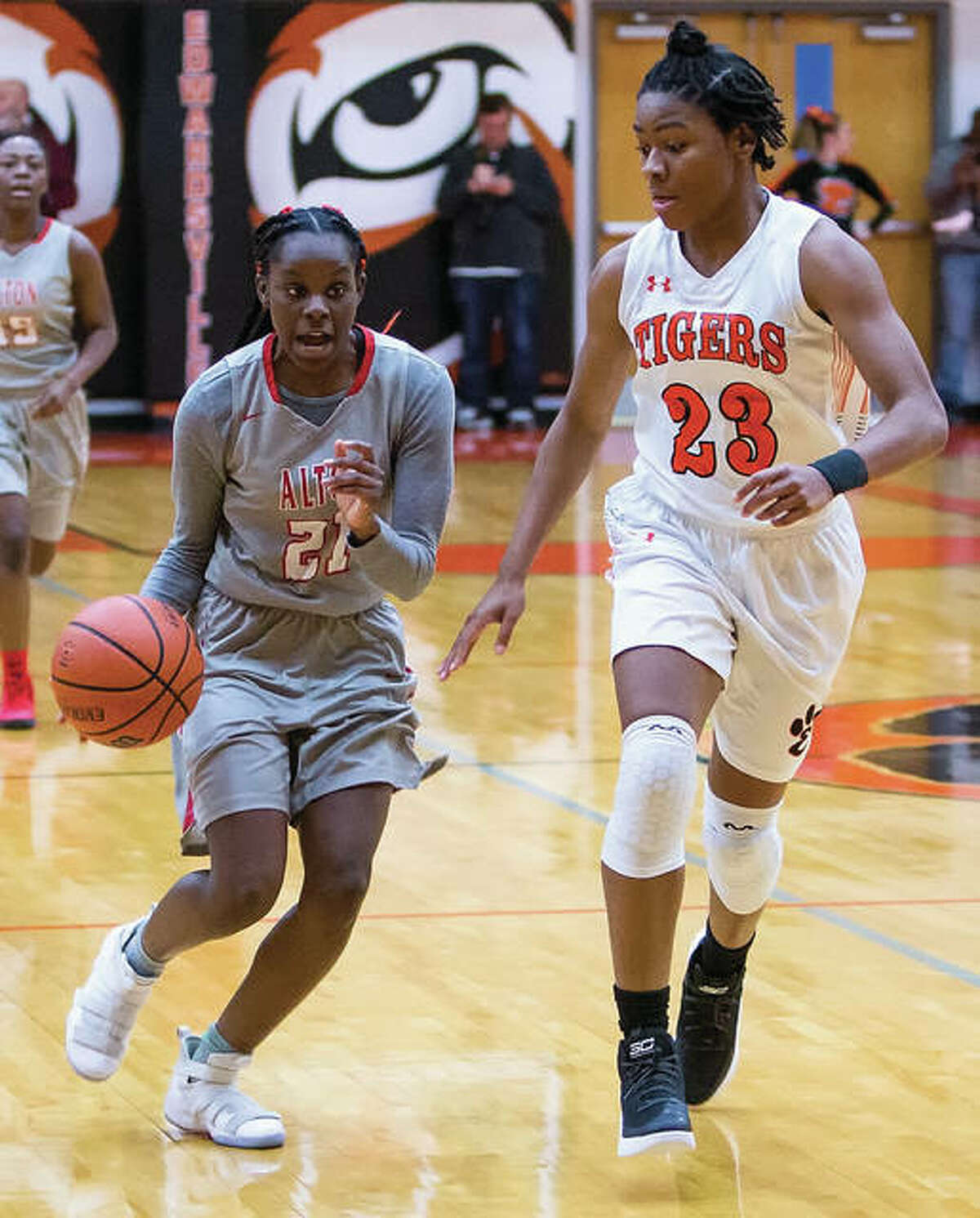 Alton's Laila McNeal (left) pushes the ball upcourt while being defended by Edwardsville's Myriah Noodel-Haywood during a SWC girls basketball game Friday night in Edwardsville.