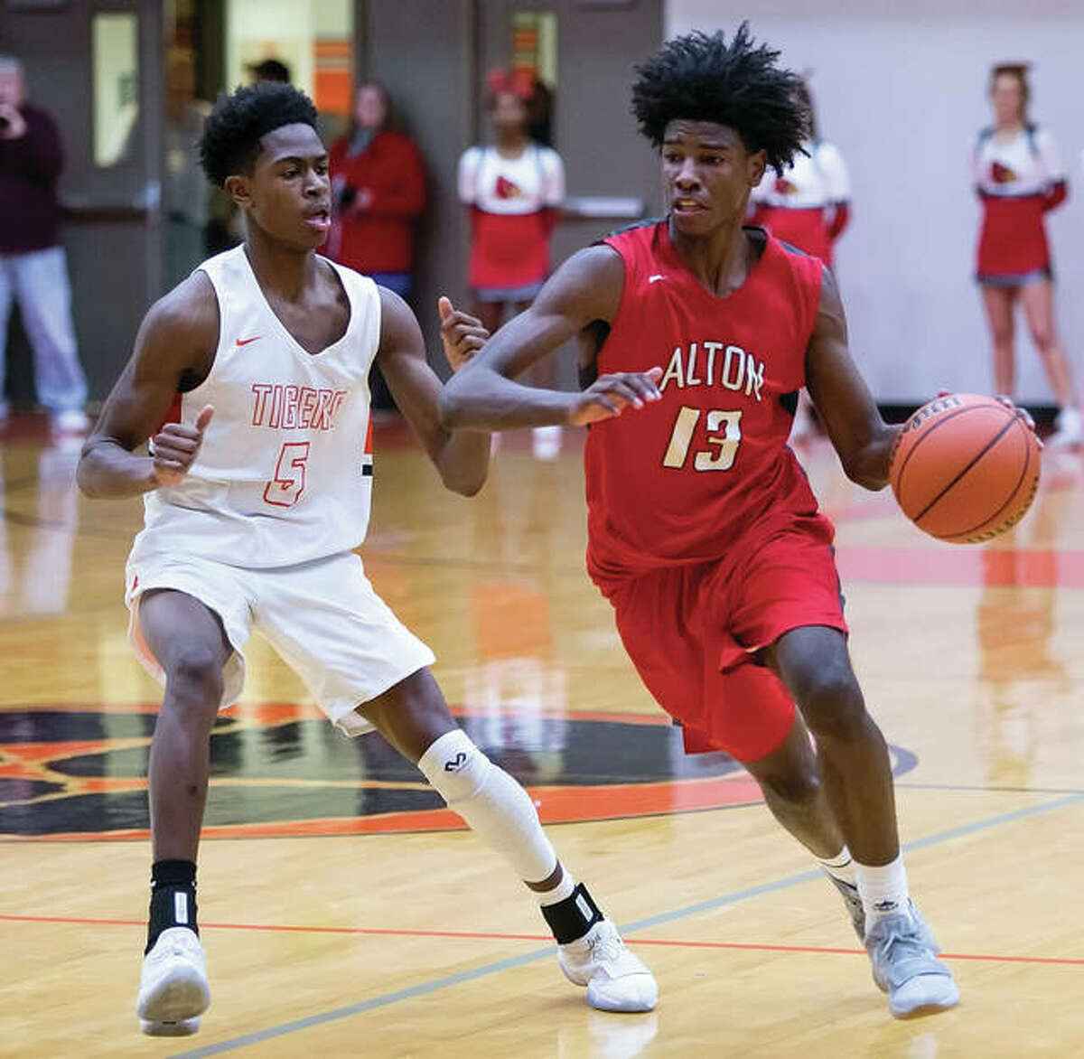 Alton's Malik Smith (right) dribbles past Edwardsville's Lavontas Hairston during the first half Friday night in Edwardsville.