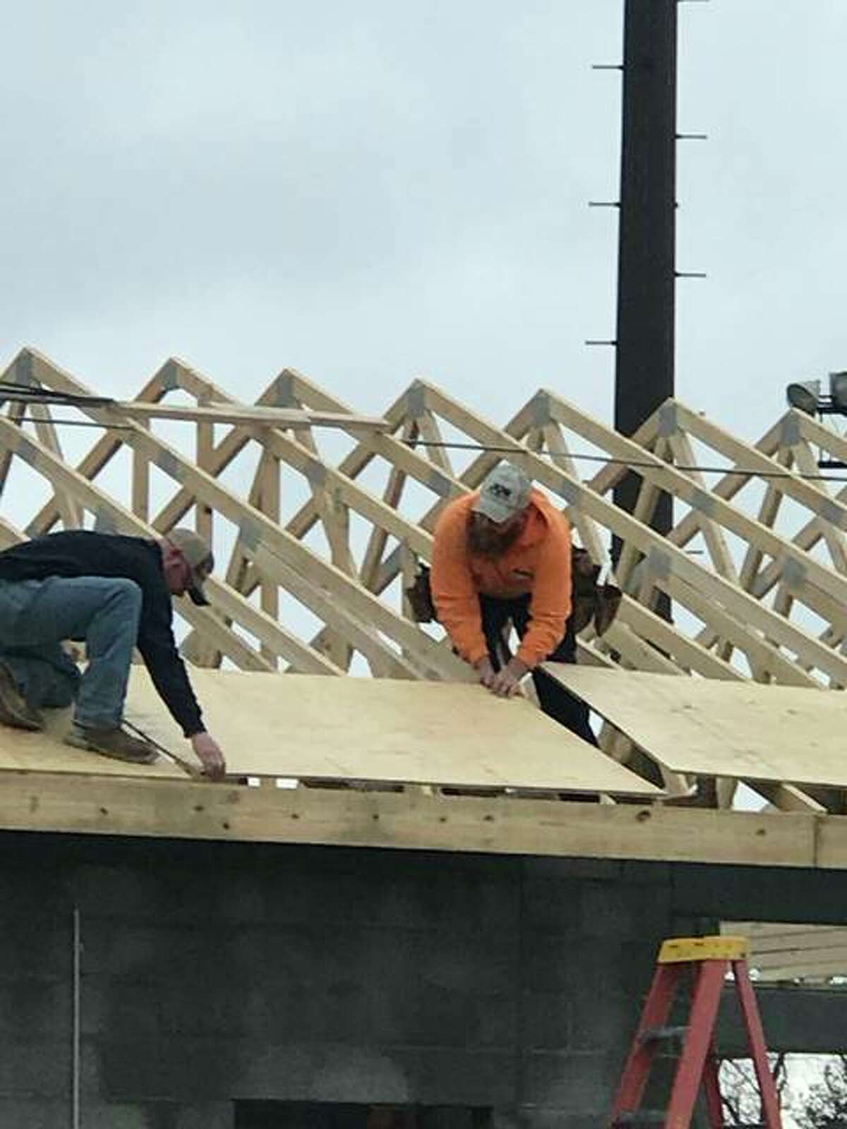 Volunteers from Jun Construction of Godfrey put up roof trusses and sheeting on the evolving concession and restroom building at Gordon F. Moore Park on Wednesday, Jan. 10. The $300,000 structure is one of 12 of the most significant projects for which the city issued a building permit in 2017.