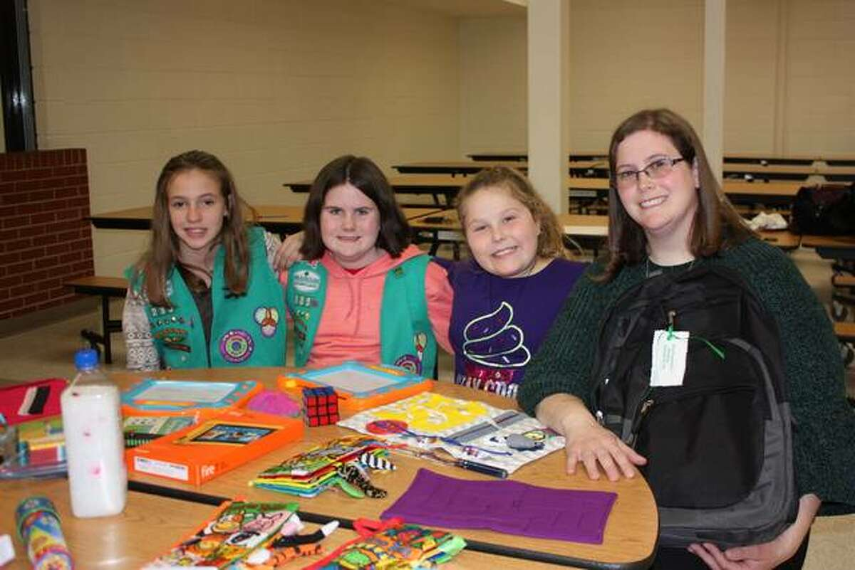 From left, Girl Scout Juniors Layla Hall, Hannah McQuay and Jillian Adams, along with Tasha McQuay, a troop leader, help put together sensory resource kits to help special needs students maximize their experience during van rides.