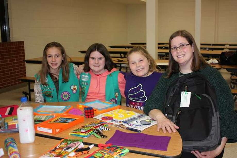 From left, Girl Scout Juniors Layla Hall, Hannah McQuay and Jillian Adams, along with Tasha McQuay, a troop leader, help put together sensory resource kits to help special needs students maximize their experience during van rides. Photo: For The Telegraph