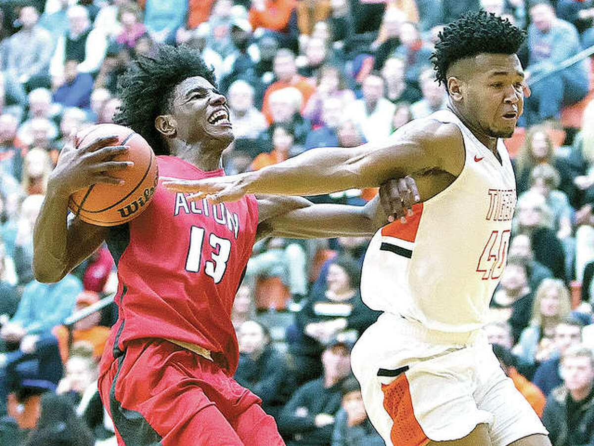 Alton's Malik Smith (left) fends off Edwardsville's R.J. Wilson before going up for a shot during a Southwestern Conference boys basketball game Friday night at Lucco-Jackson Gym in Edwardsville. The Redbirds won 55-50 in overtime to halt a four-game losing streak and improve to 10-5.