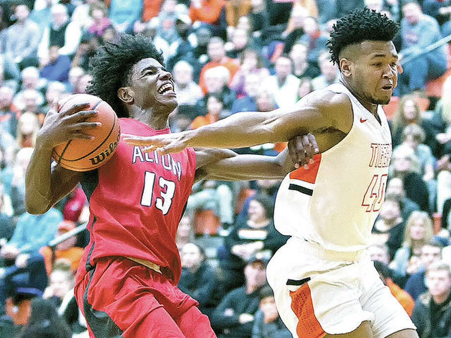 Alton's Malik Smith (left) fends off Edwardsville's R.J. Wilson before going up for a shot during a Southwestern Conference boys basketball game Friday night at Lucco-Jackson Gym in Edwardsville. The Redbirds won 55-50 in overtime to halt a four-game losing streak and improve to 10-5. Photo: Scott Kane | For The Telegraph