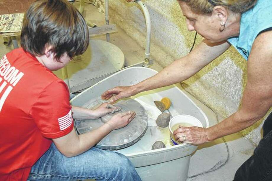 Eli Stock (left) takes instruction from Kirby Drennan on how to center the clay on a pottery wheel Saturday at Strawn Art Gallery. Photo: Greg Olson | Journal-Courier