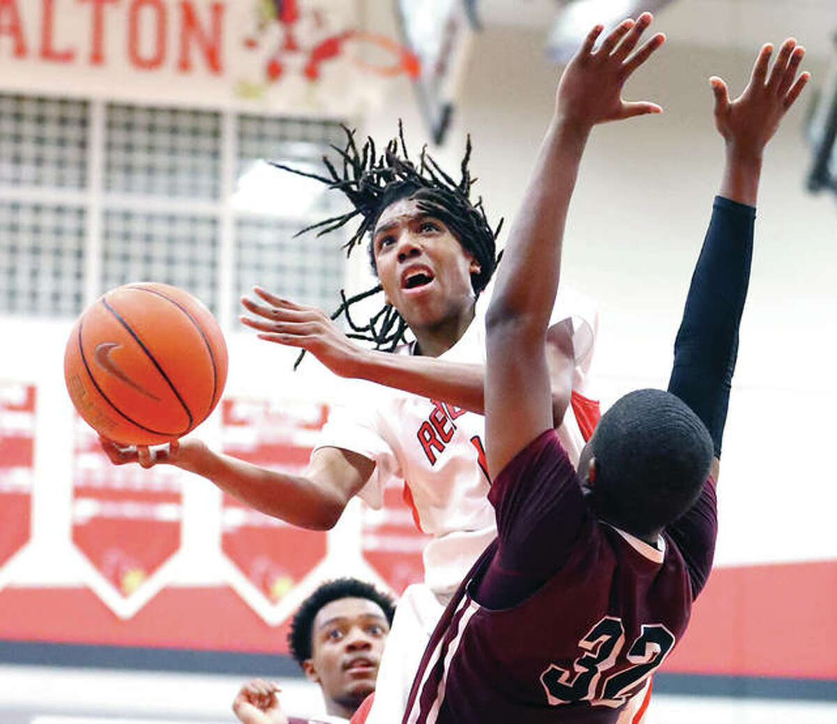 Alton's Donovan Clay and the Redbirds opened tourney play at Belleville East on Tuesday night with a loss to Champaign Central. He is shownshooting around Belleville West's E.J. Liddell (right) during a SWC game Jan. 5 at Alton High.