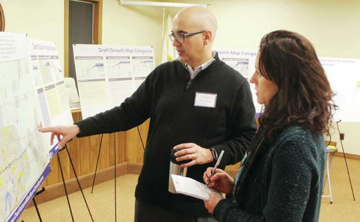 Christine Favilla, representing the Sierra Club, listens as Stephen Ibendahl, a consultant, talks about a proposed update of Madison County's comprehensive plan at an open house Tuesday in Bethalto.