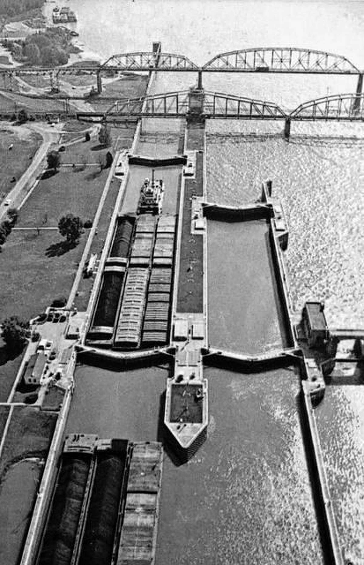 Barges pass through the Locks and Dam 26 at the Alton riverfront. The old Clark Bridge and railroad can also be seen.