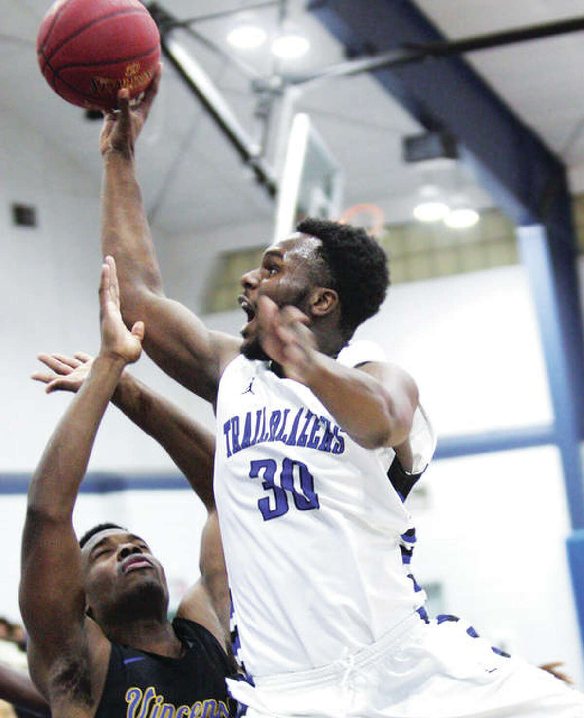 Lewis and Clark's Raymond Smith (30) goes up and over Vincennes University's George Dixon for a basket Wednesday night at LCCC.