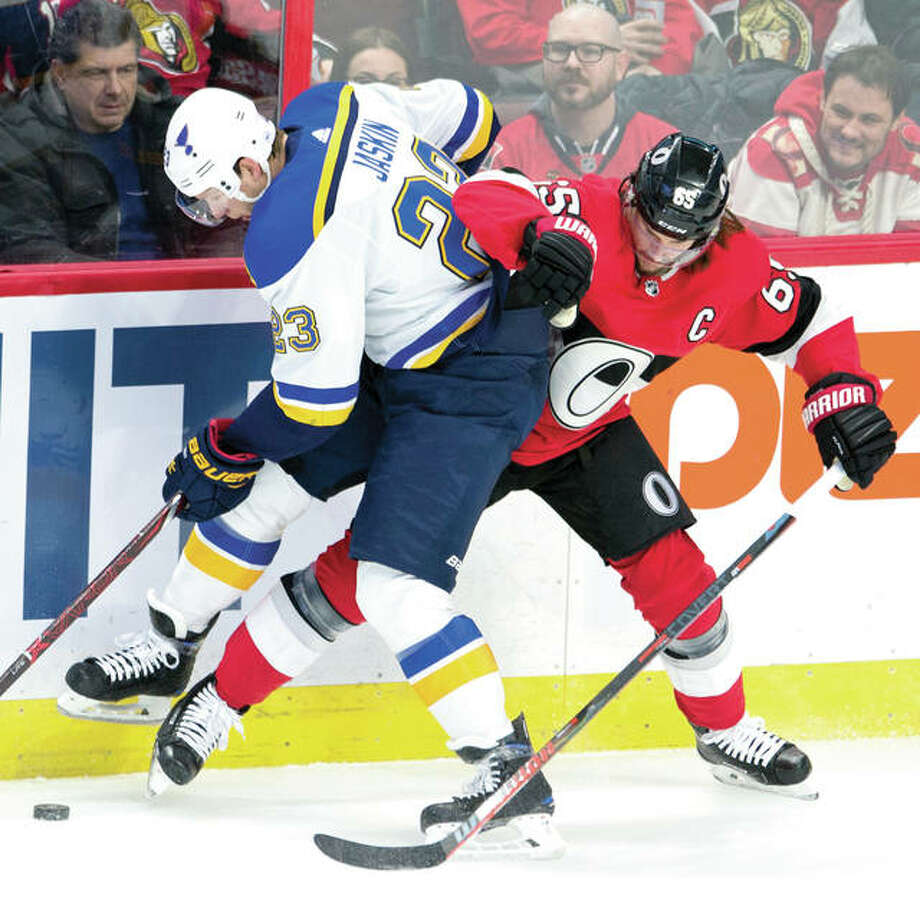 Ottawa defenseman Erik Karlsson (65) battles with the Blues' Dmitrij Jaskin along the boards during Thursday night's game in Ottawa, Ontario. Photo: AP