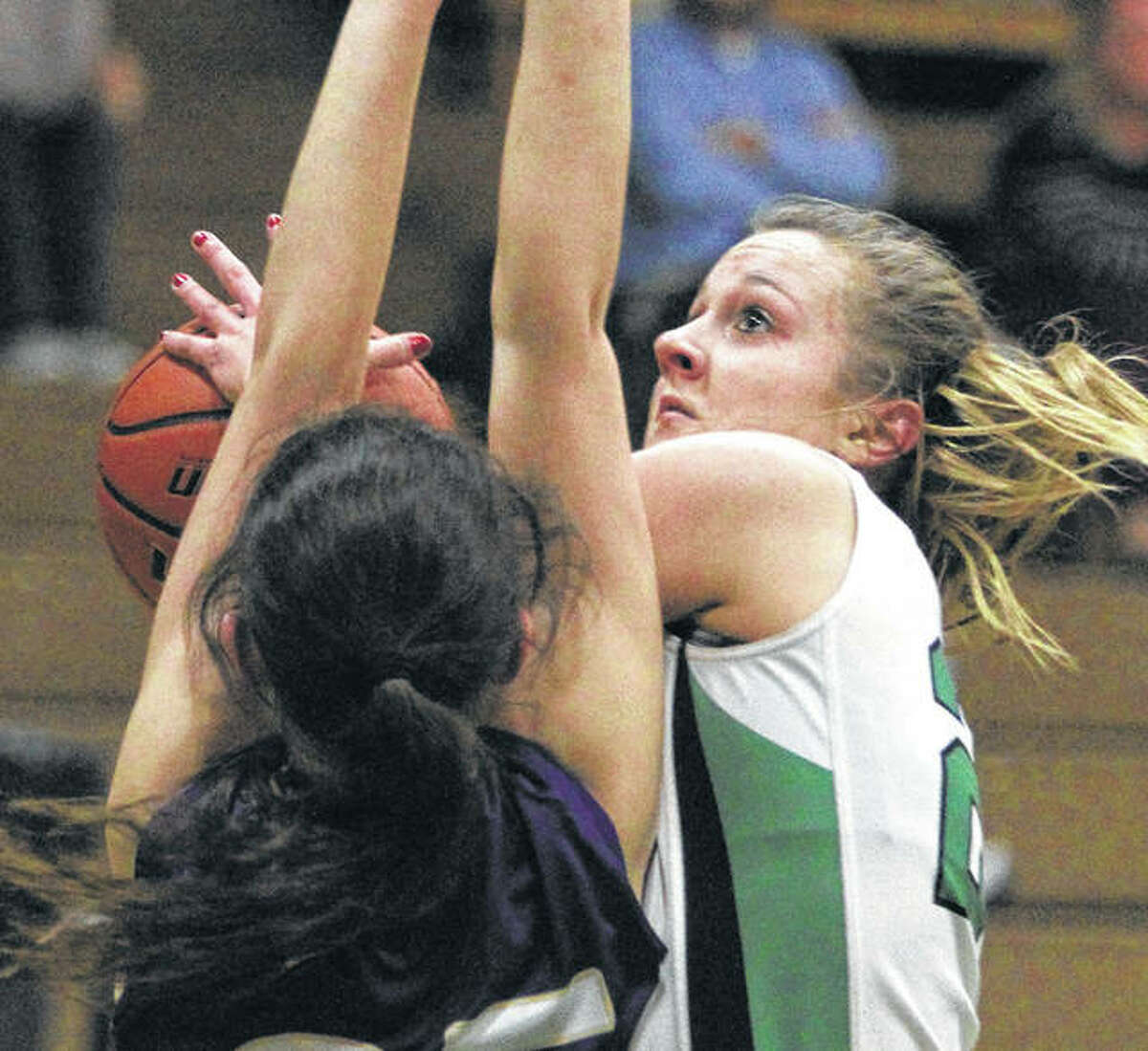 Carrollton junior Hannah Krumwiede (right) shoots over a Jacksonville Routt defender during Thursday's WIVC girls basketball game in Carrollton. Krumwiede scored her 1,000 career point in the Hawks' loss.
