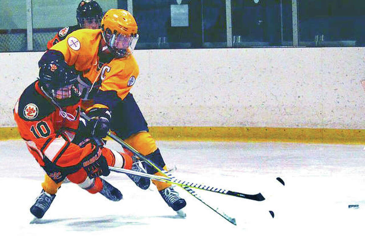 Edwardsville forward Mitchell Oberlag (10) gets a shot off as he is checked by a De Smet player during the second period of Thursday's Mid-States Hockey Association game at Queeny Park in St. Louis.