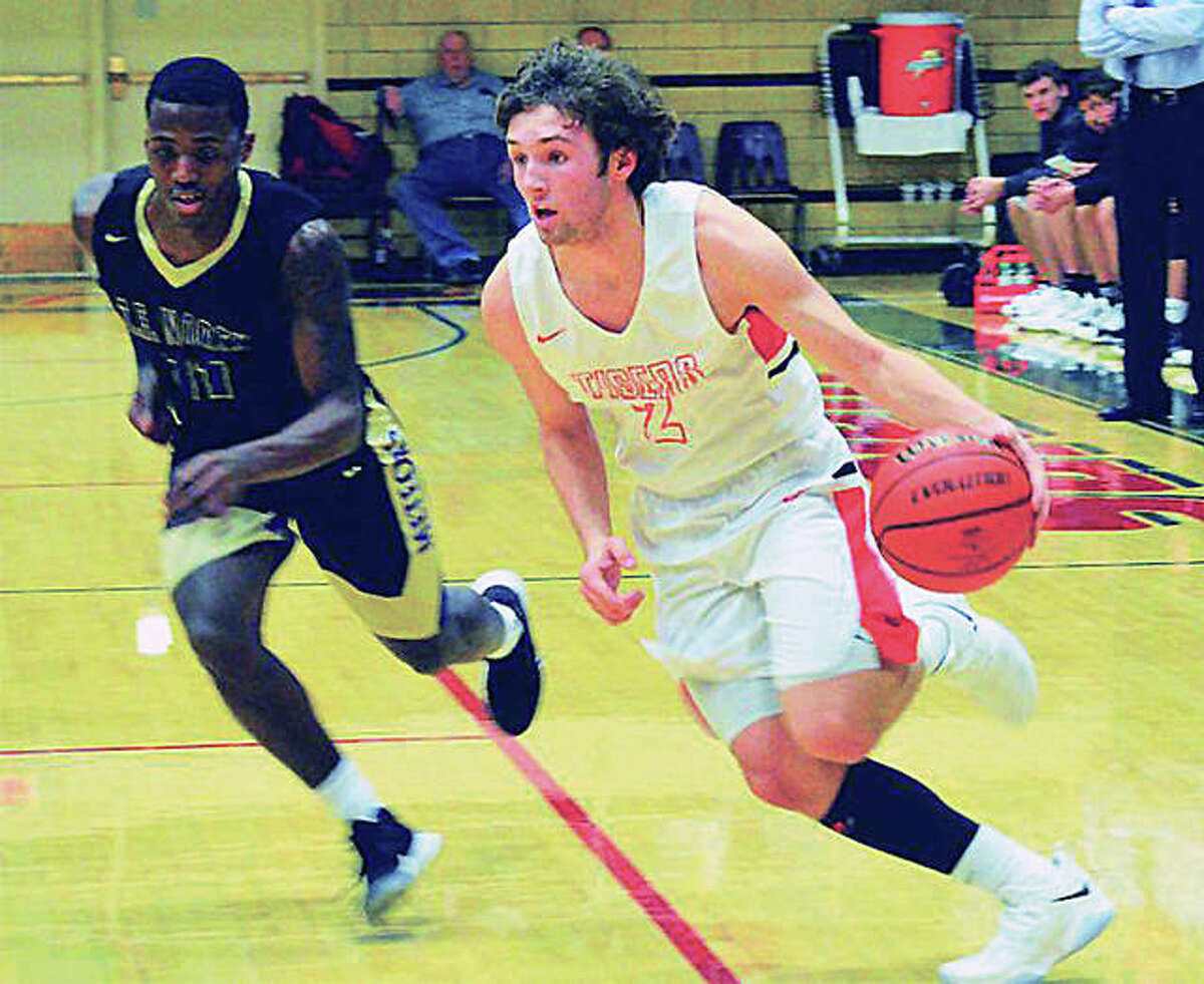 Edwardsville's Jack Marinko (right) drives past a Thornton Fractional North defender during a first-round game at the Salem Tournament on Thursday night at B.E. Gum Gym. Marinko scored 35 points in the Tigers' victory.