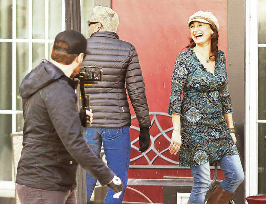 "A photographer with the internet-based show, ""Small Business Revolution-Main Street,"" films Alton Main Street Executive Director Sara McGibany, right, sharing a laugh with the program's Amanda Brinkman, left, during a walking tour of Downton Alton Friday. Alton is vying for a business revitalization prize of $500,000 after being selected as one of the 10 towns chosen for the possible featured spot on the show and winning of the money that will help revitalize small businesses in historic downtown communities. Photo: John Badman