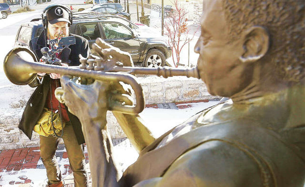 A photographer for the show films the Miles Davis statue on E. Third Street in Downtown Alton Friday during a downtown walking tour with officials vying for the prize money.