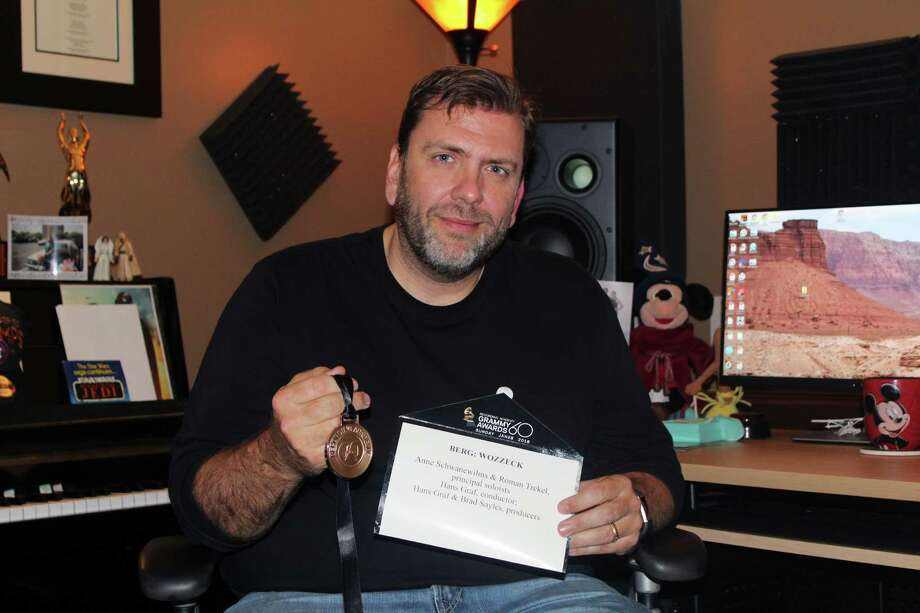 "Kingwood resident Brad Sayles holds up a medal presented to Grammy winners, and the card announcing ""Berg: Wozzeck"" winner of the best recorded opera in his home studio in Kingwood on Wednesday, Jan. 31. Photo: Melanie Feuk"
