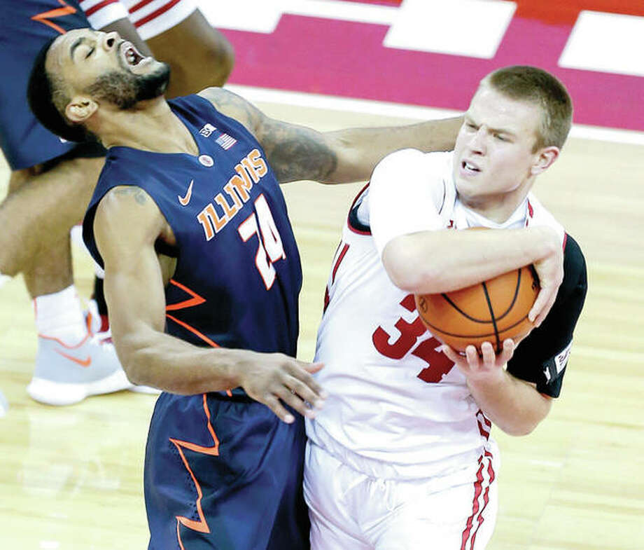 Wisconsin's Brad Davison (34) fouls Illinois' Mark Alstork (24) Friday's game in Madison, Wis. Photo: AP
