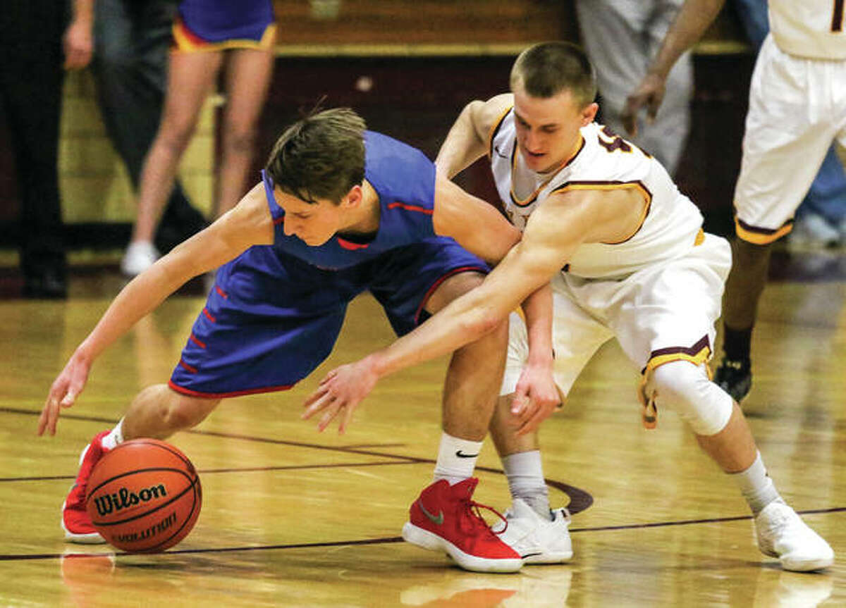 Roxana's Andrew Beckman (left) tries to retain possession of the ball while East Alton-Wood River's Justin Englar reaches in during a Dec. 8 boys basketball game at Memorial Gym in Wood River. The Oilers won that game, but the Shells won the rematch Friday night in the 11th-place game at the Litchfield Tournament.