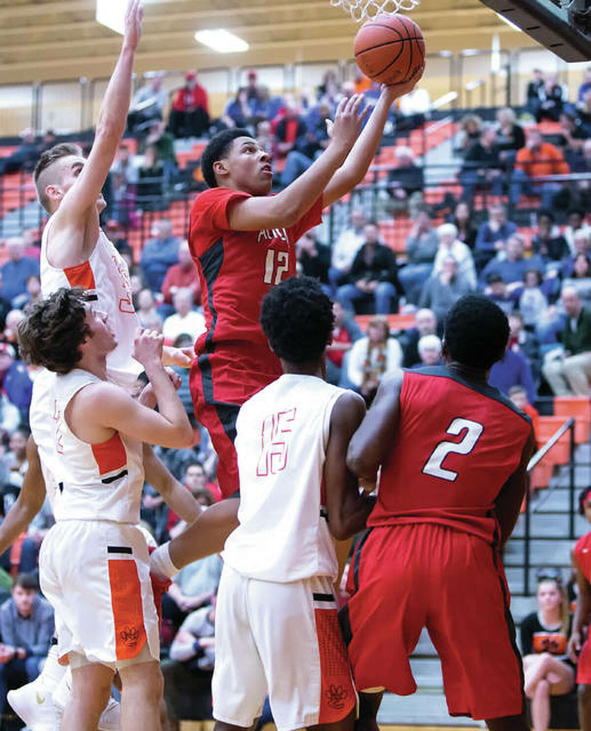 Alton's Josh Rivers (middle) goes to his left hand for two points after getting inside Edwardsville defenders (from left) Caleb Strohmeier, Jack Marinko and Jaylon Tuggle while the Redbirds' Kevin Caldwell Jr. (2) watches the play during Alton's overtime win on Jan. 12 at Lucco-Jackson Gym in Edwardsville. Both the Redbirds and Tigers spent the week in tournament action. While Edwardsville played Centralia for the title at the Salem Tourney late Saturday night, Alton completed play at the Belleville East Chick-fil-A Classic by defeating Columbia 64-56 in the seventh-place game at Belleville. The Redbirds salvaged one win from the tourney after being upset by Belleville Althoff in Thursday's consolation semifinals. Alton, which had lost six of its previous seven games, improved to 11-7. Kevin Caldwell Jr. scored 25 points, Malik Smith had a double-double with 22 points and 13 rebounds, and Donovan Clay chipped in 11 for the Redbirds. Columbia is 10-9.