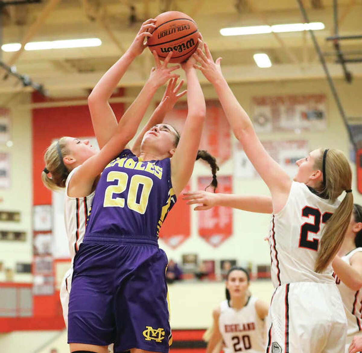 CM's Anna Hall (20) battles Highland's Rece Portell (left) and Lauren Baer (right) for a rebound during an Eagles win game Dec. 20 in Highland. The Eagles made it 2-0 vs. the Bulldogs on Saturday with a win in the third-place game of the Highland Tourney.