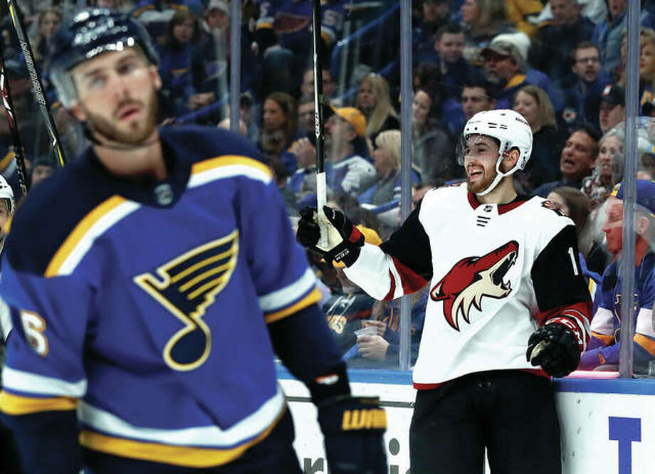 Arizona's Brendan Perlini (right) celebrates after scoring as the Blues' Joel Edmundson skates past during the first period Saturday night in St. Louis.